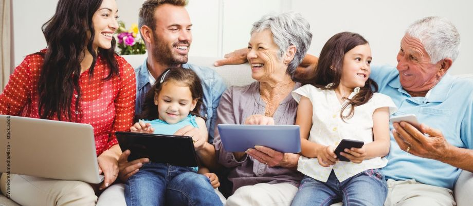 Family smiling while holding technologies
